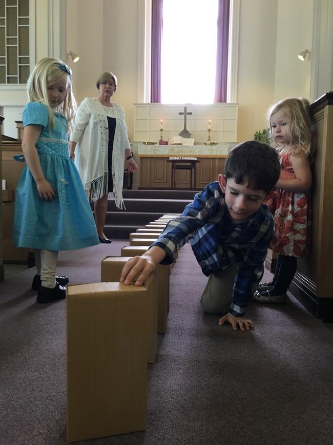 Children setting up dominoes