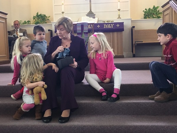 Children learning about the symbol of the donkey on Palm Sunday