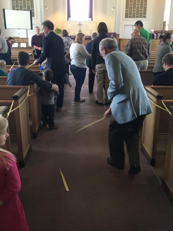 Congregation laying palms on tha aisle.