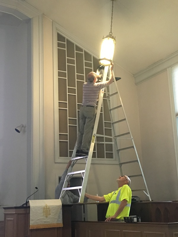 Installing new lights during Church Work Day.
